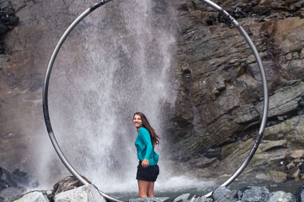 Jumping into the waterfall pool framed by a cyr wheel