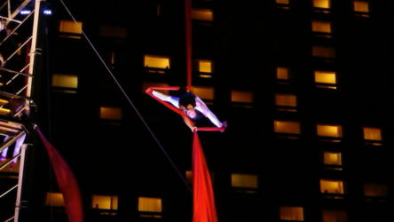 Splits upside down hanging from red silks at night
