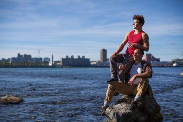 Sylvain sitting on Micah on rock in river